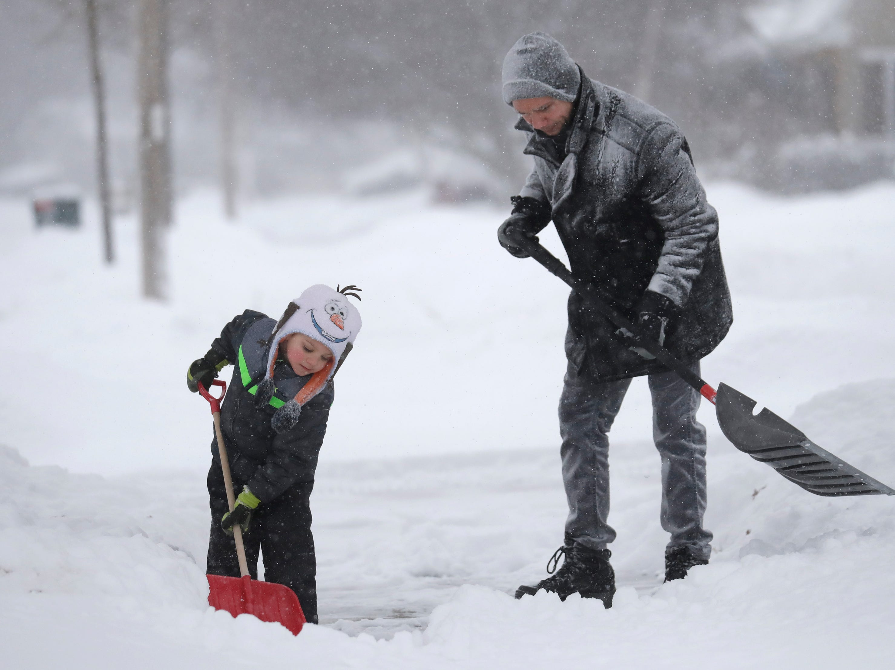 David Liebhard gets a little help from his son Levi, 4, as the two shovel their driveway during a snowstorm Monday, January 28, 2019, in Appleton, Wis.
