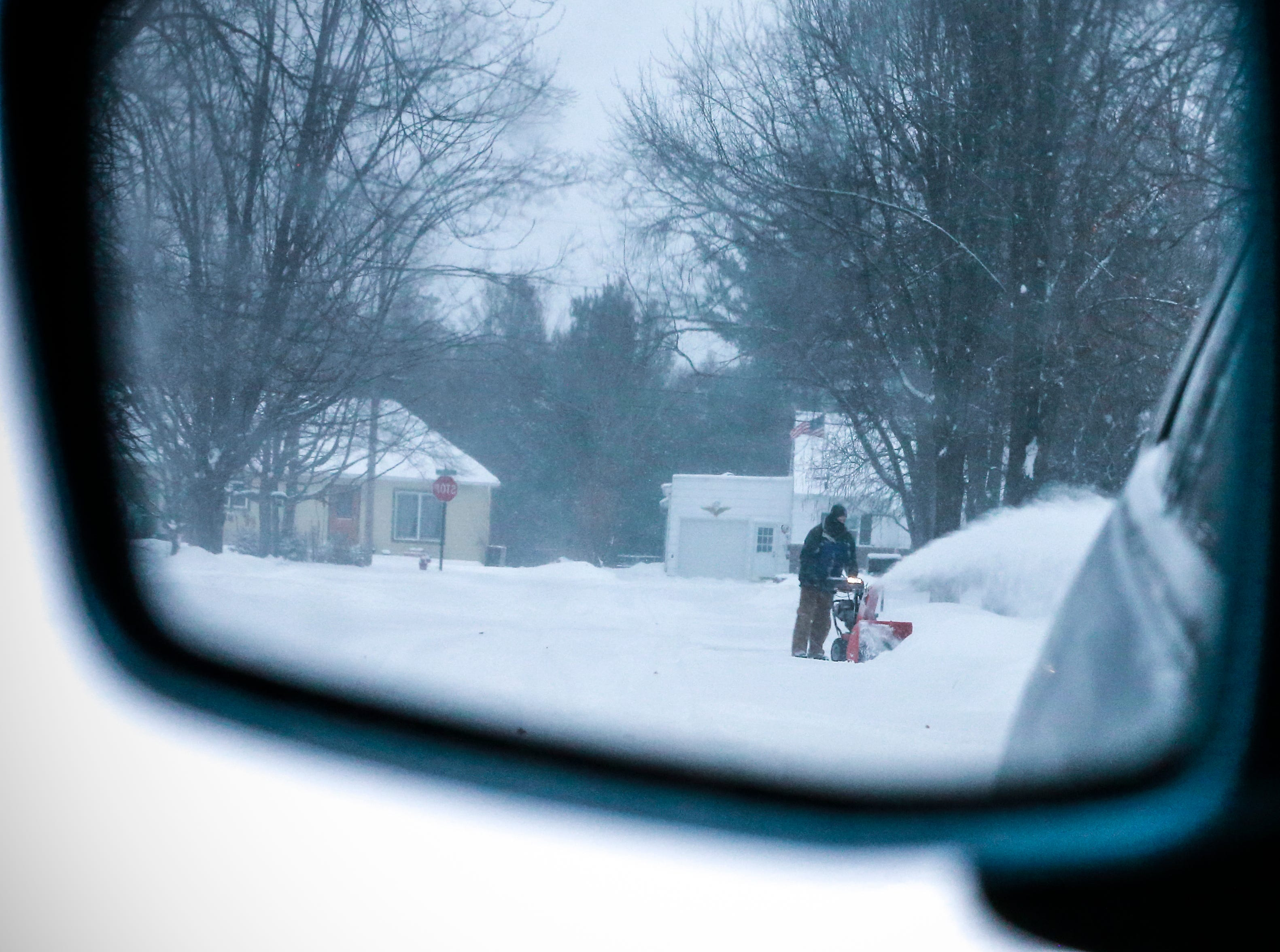 Tom Schnider operates his snowblower to clear snow off his driveway after a snowstorm Monday, Jan. 28, 2019, in Wausau, Wis.