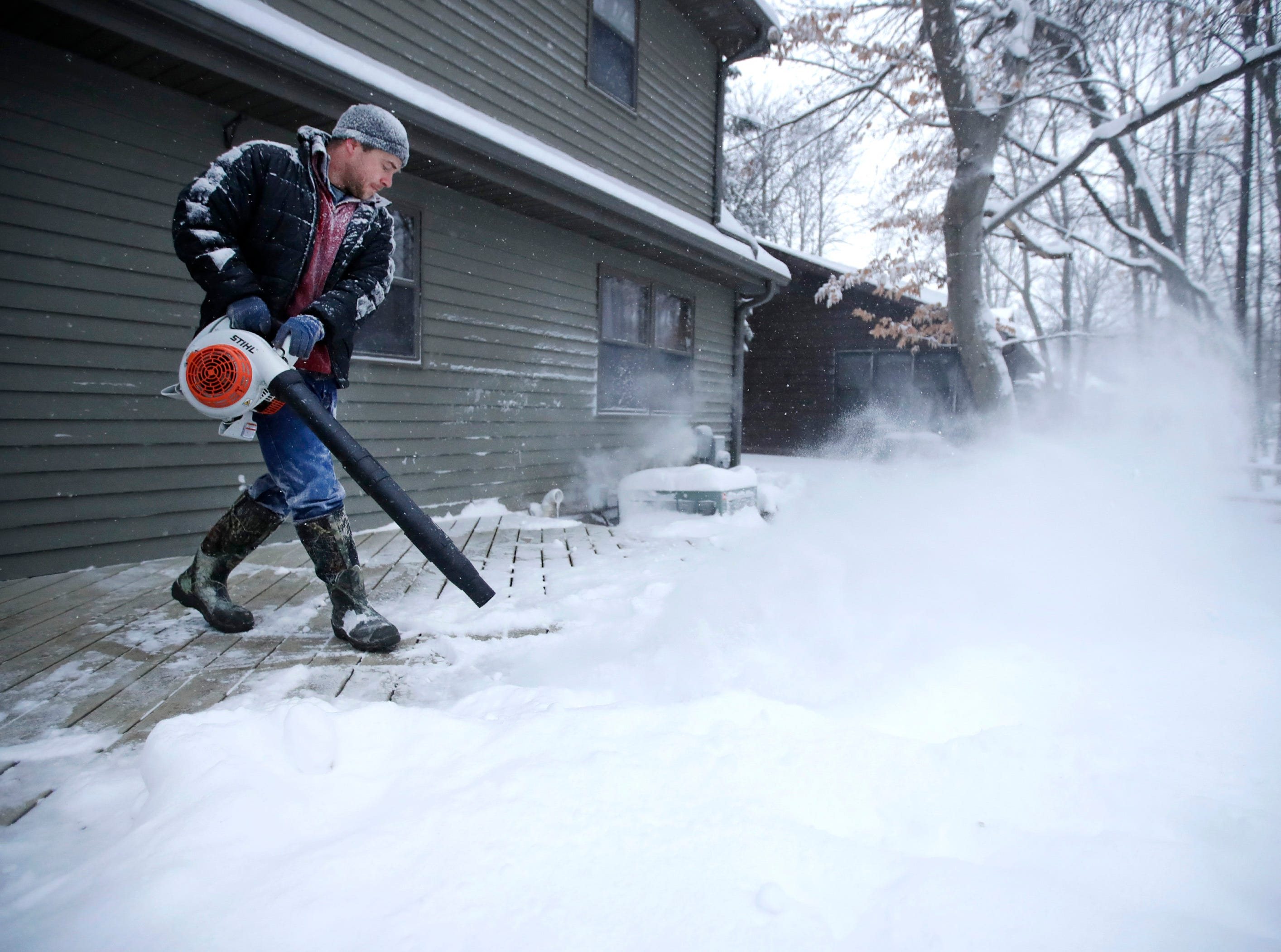 Kurt Zuleger, of Appleton, uses a leaf blower to clear the snow from his deck Monday, Jan. 28, 2019, in Appleton, Wis.