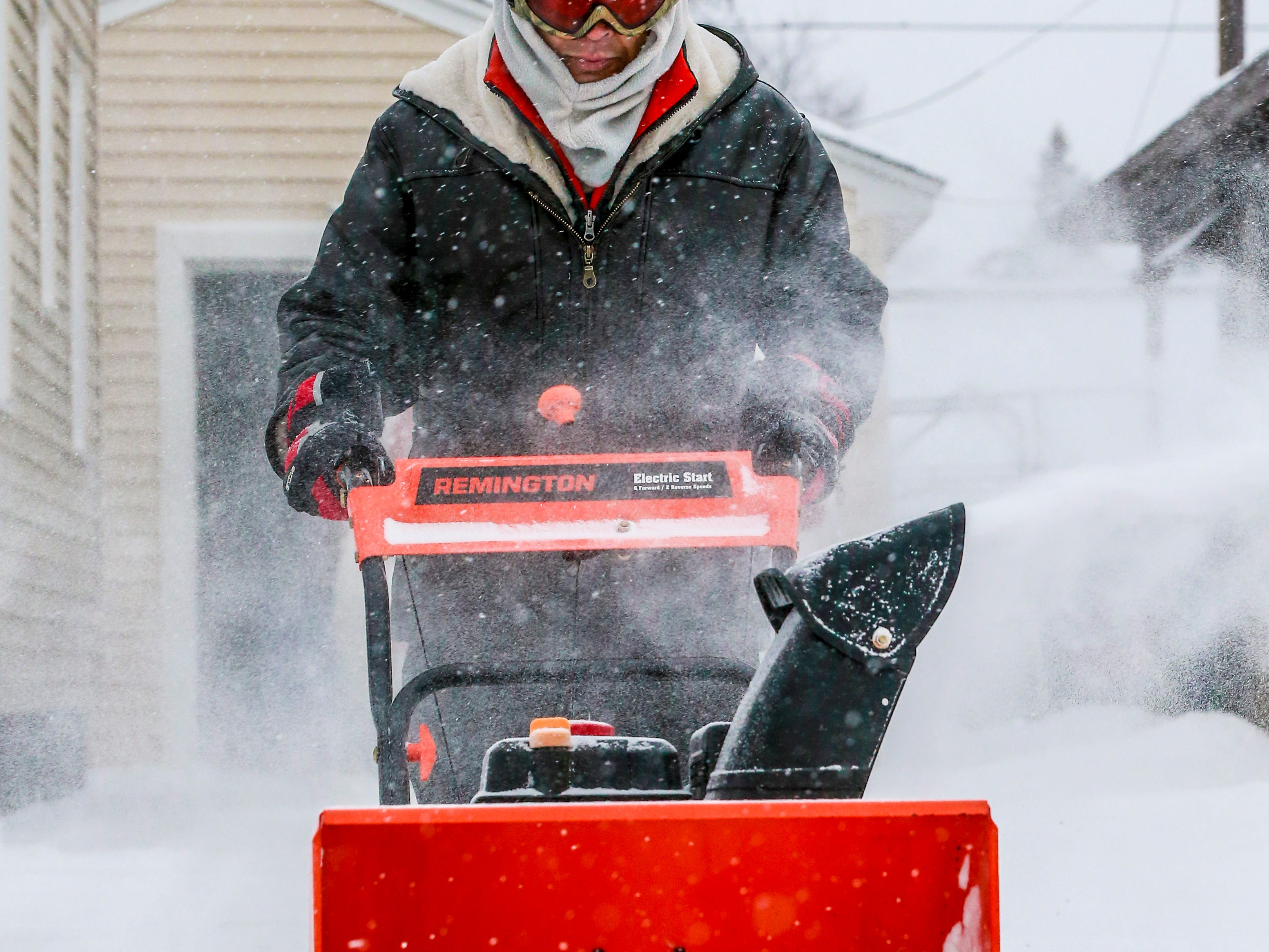 Vichai Gillette blows snow off from his driveway after a snowstorm Monday, Jan. 28, 2019, in Wausau, Wis.
