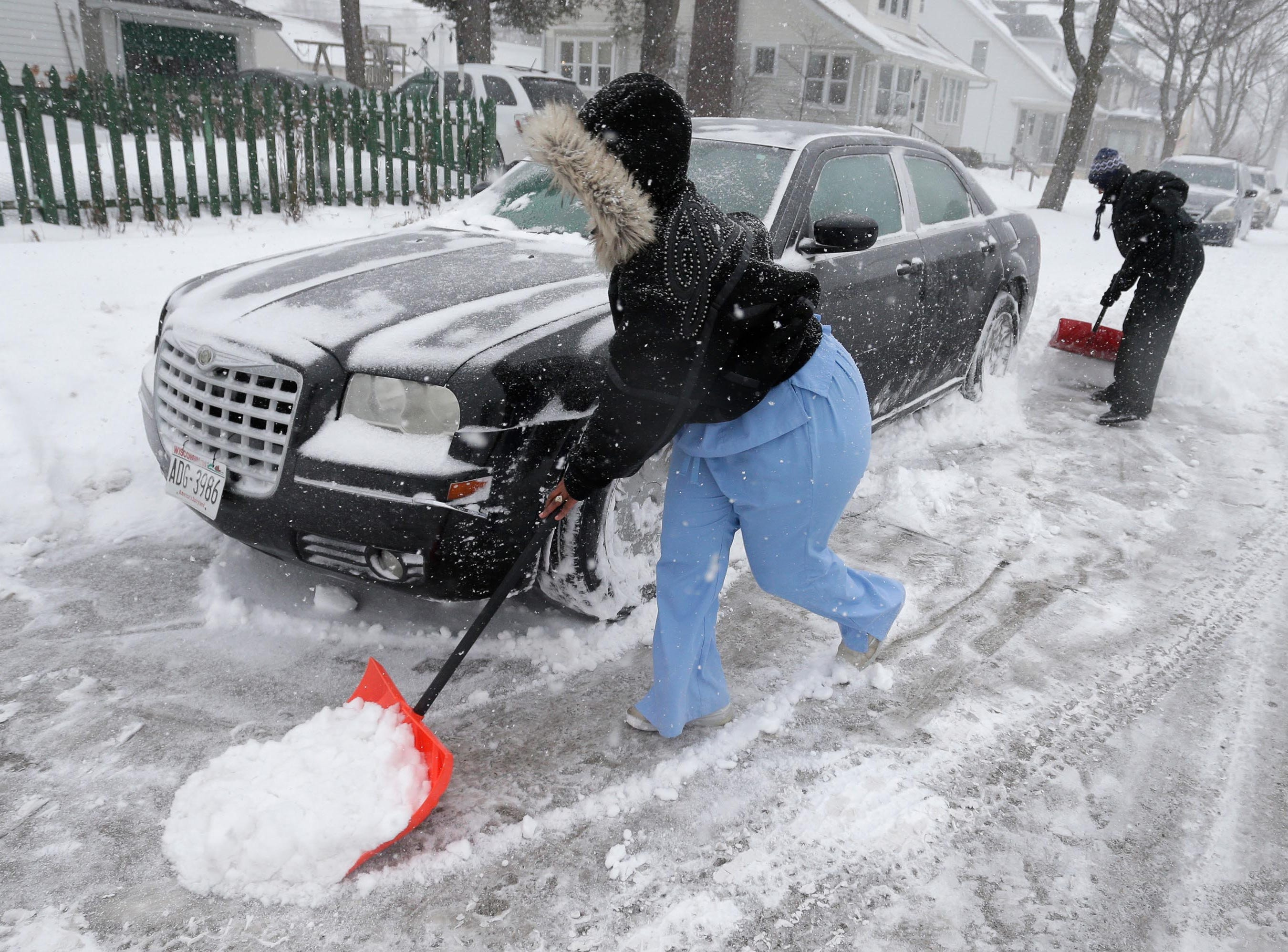Ananomi Johnson of Sheboygan, left, and Wendy Wilson of Sheboygan, clear snow from around Johnson's car on South Eighth Street on Monday, Jan. 28, 2019, in Sheboygan, Wis. Wilson said that it was too much snow at one time.
