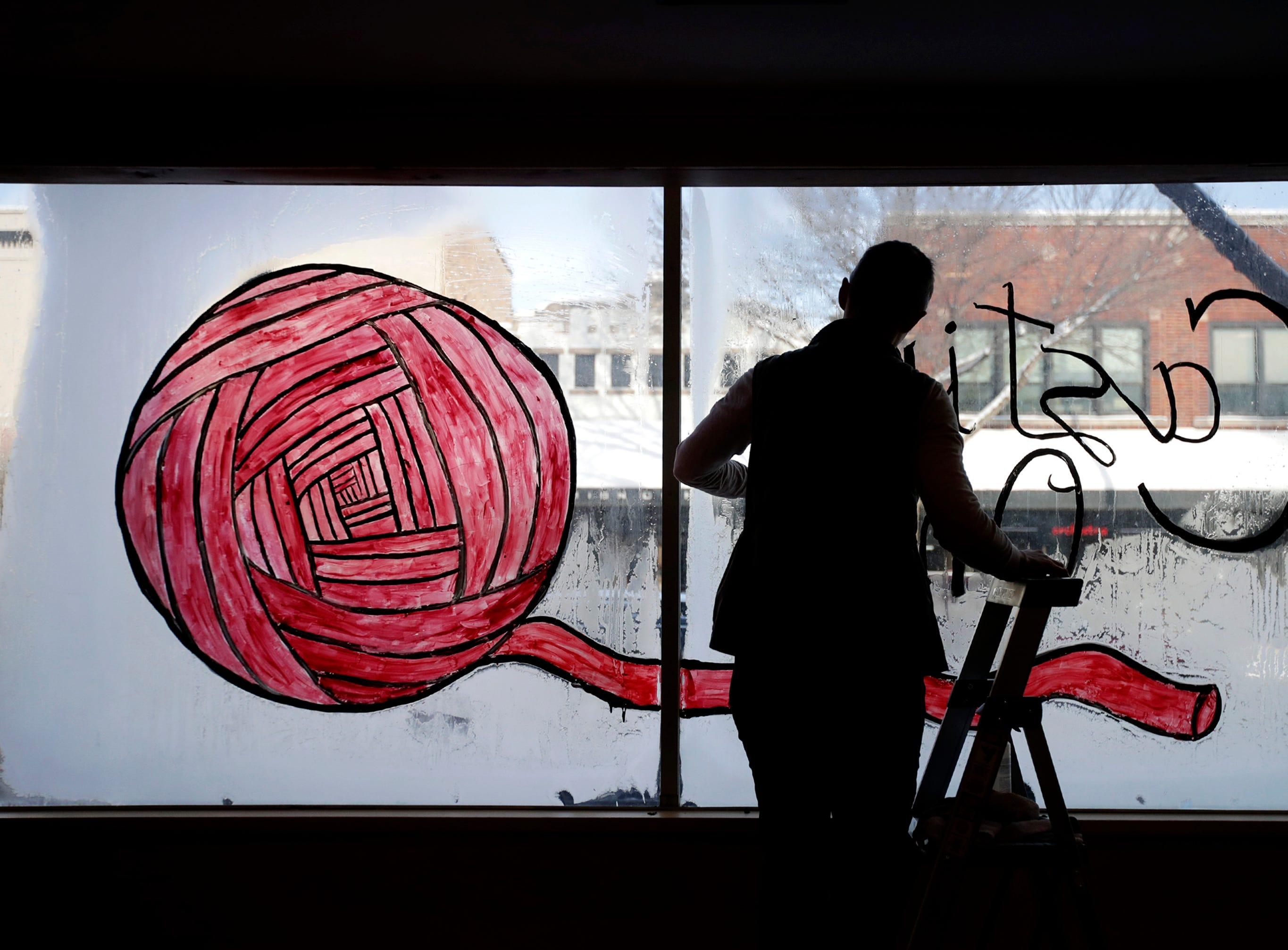 Sam Rabideau, co-owner of Casting On, scrapes their temporary sign off the front window Friday, Jan. 25, 2019 in preparation for their soft opening on Saturday, Jan 26, in Appleton, Wis.