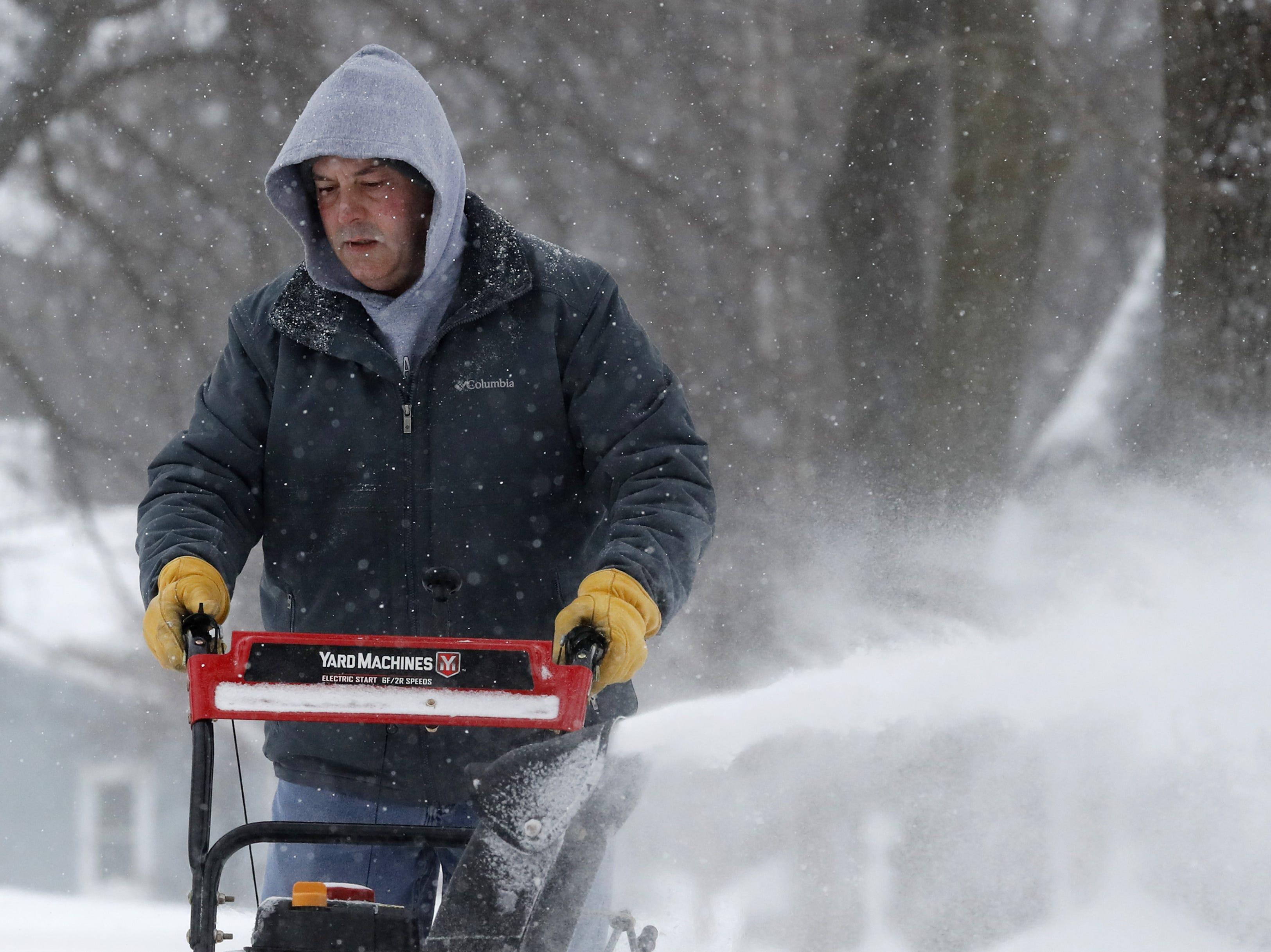 Jerry Lincoln, of Menasha, snowblows a neighbor's sidewalk Monday, Jan. 28, 2019, in Menasha, Wis.