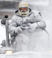 Jeff Kluever, with Pfefferle Management, is caked with snow as he clears a sidewalk in downtown Appleton Monday, Jan. 28, 2019, in Appleton, Wis.