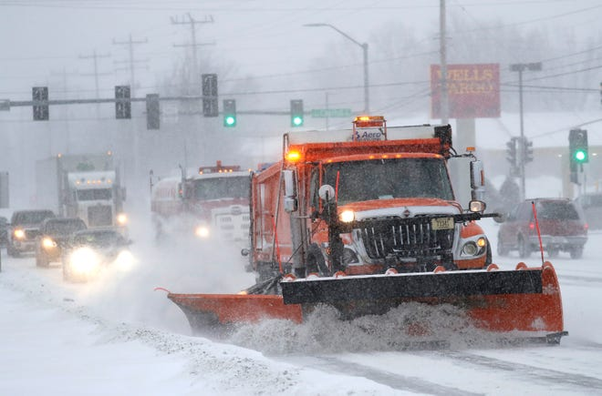 A plow clears snow for traffic along Ballard Road during a snowstorm Monday, Jan. 28, 2019, in Appleton, Wis.