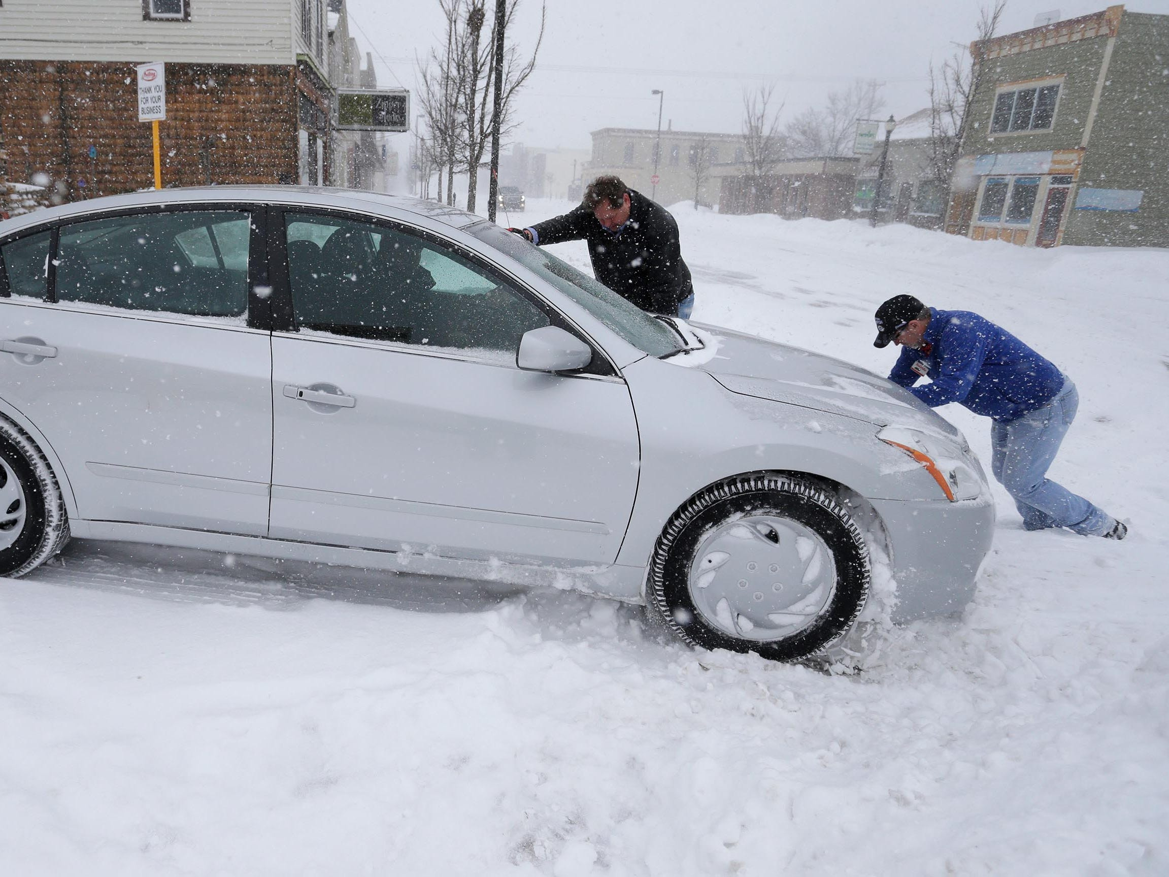 Trilling True Value's Greg Parmly, left, and Chris Schramm, help push a customer's car out of a snow bank, Monday, Jan. 28, 2019, in Sheboygan, Wis. Parmly said that his firm sold 15 snowblowers last week in anticipation of the storm.