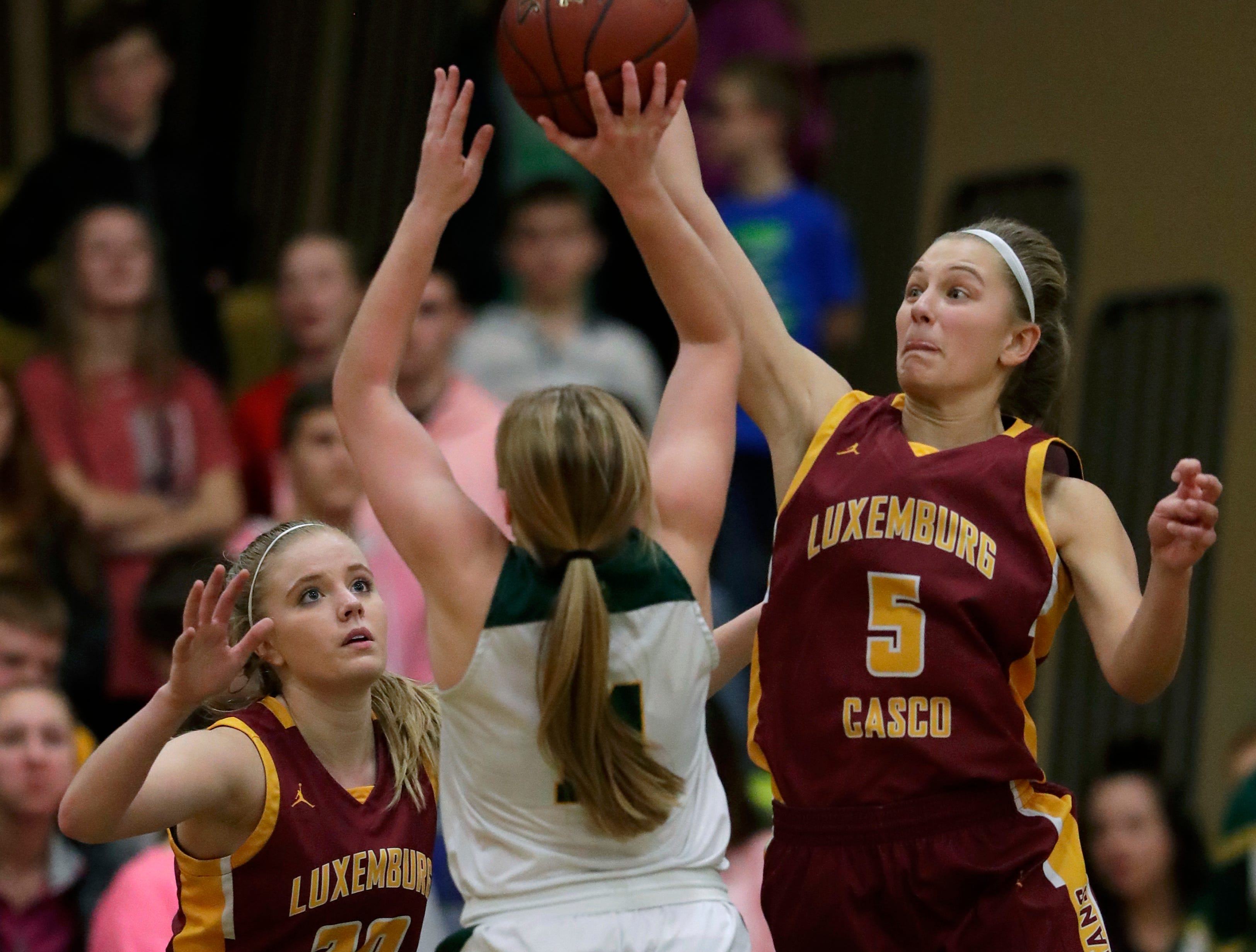 Luxemburg-Casco High School's Jenna Jorgensen (5) blocks a shot against Freedom High School's Carly Peters as Carli Kollross (20) helps on defense during their girls basketball game Thursday, January 24, 2019, in Freedom, Wis. 