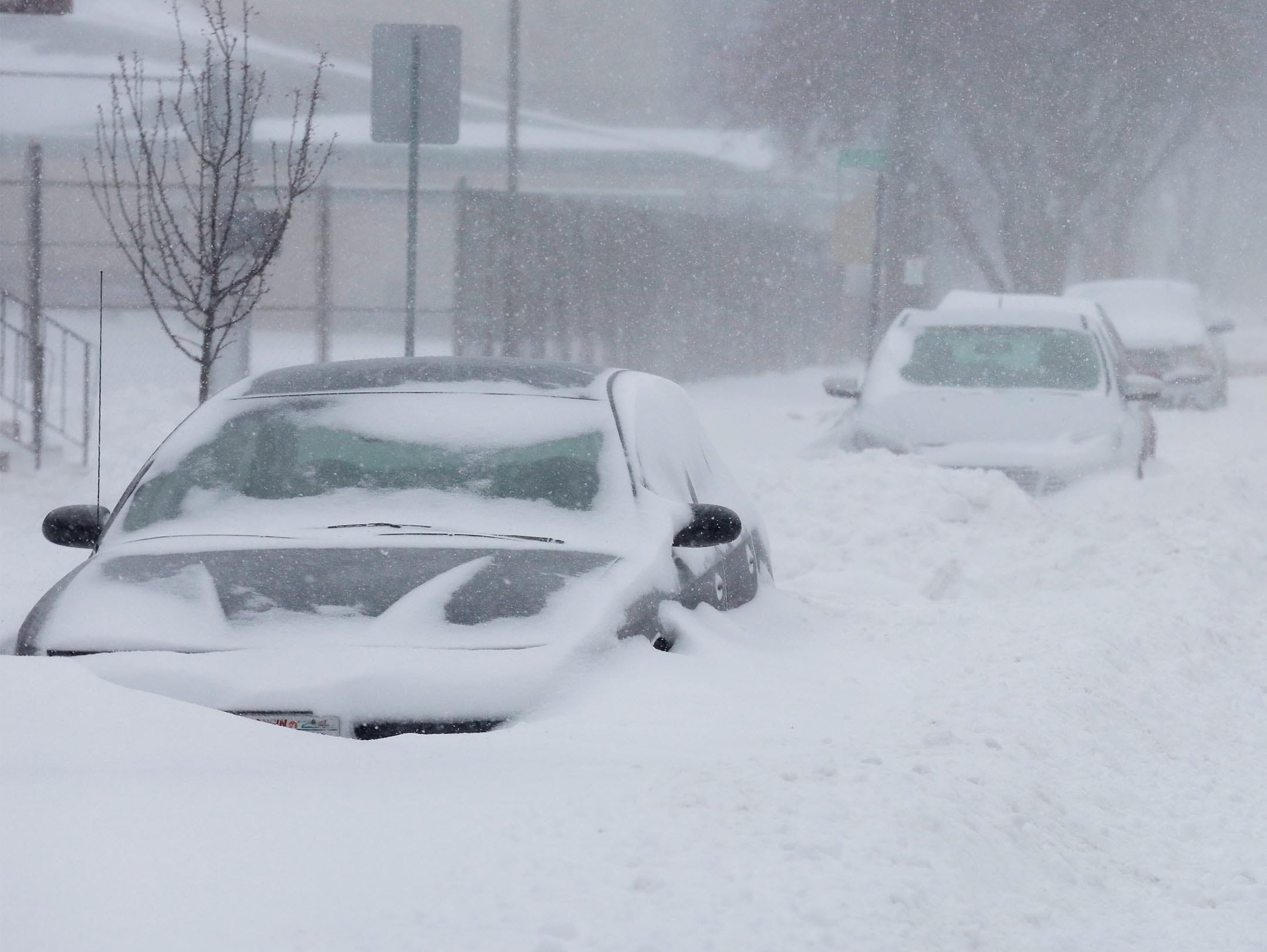 Cars are buried  in snowbanks on South Eighth Street on Monday, Jan. 28, 2019, in Sheboygan, Wis.