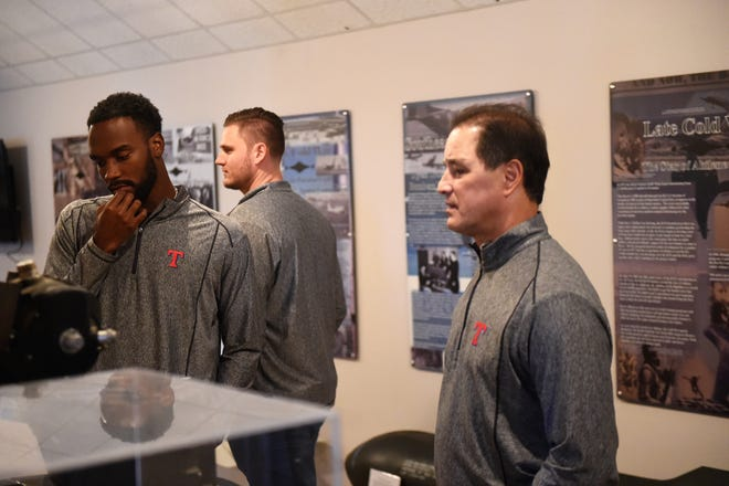 Texas Rangers Taylor Hearn, Connor Sadzeck and Don Wakamatsu look at displays at the Dyess Air Force Base Welcome Center and Museum before going on base to meet with members of the military and their families.