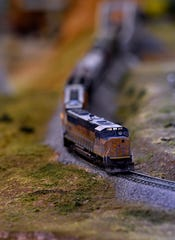 A model train makes its way through forests, cities, and plains - all within the confines of an office building.
