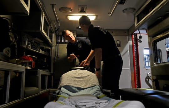 Capt. Daniel Vail and firefighter Chris Neville inside an ambulance at the Binghamton Fire Department's Hawley Street headquarters.