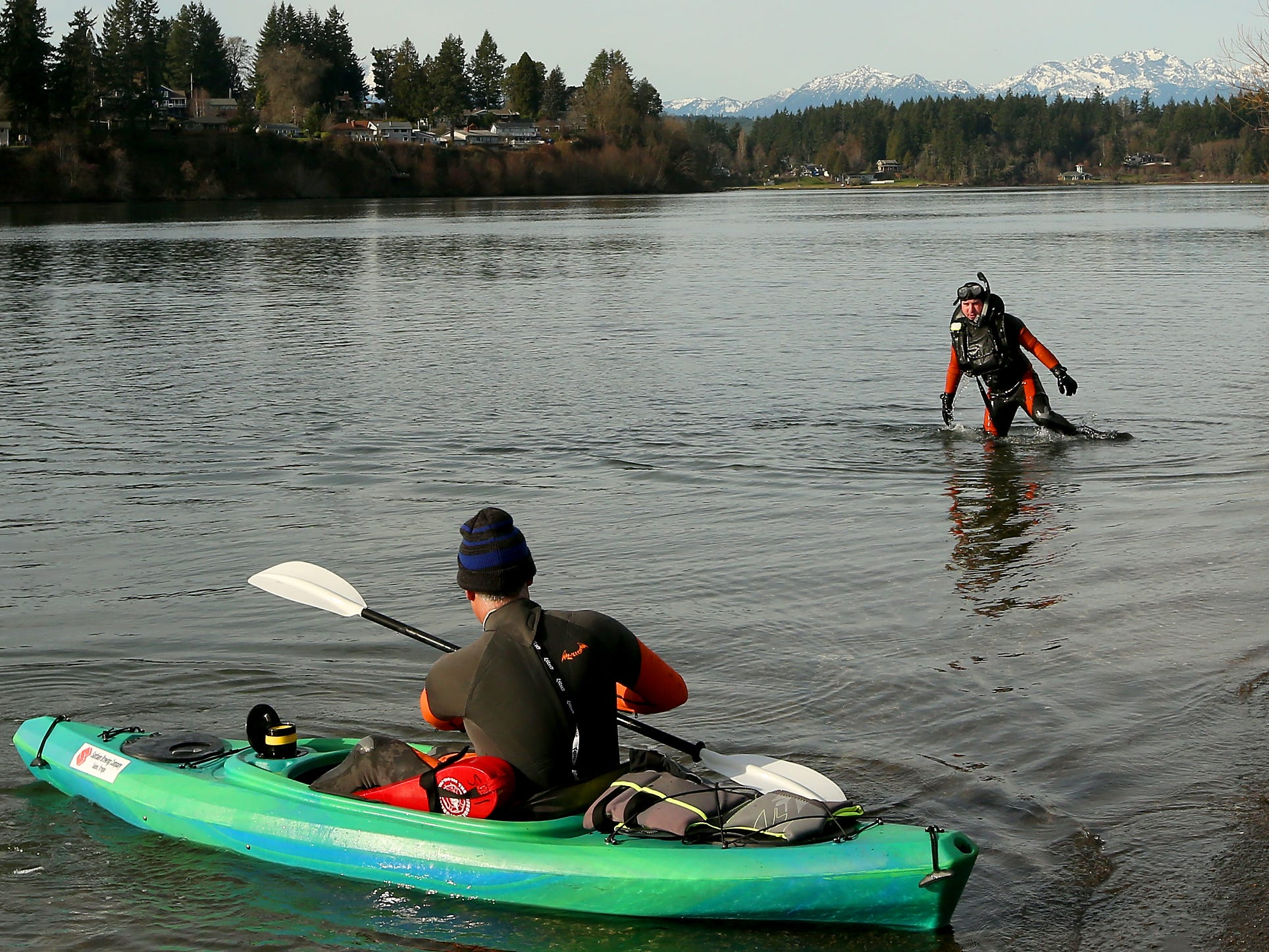 Bremerton firefighter Rickey Muttart (right) exits the water after taking part in rescue swimmer training with Lt. Alex Magallon (in the kayak) at the Lions Park Boat Launch in Bremerton on Monday, January 28, 2019.