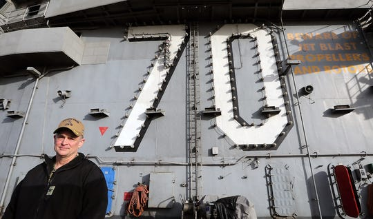 Capt. Matthew Paradise, commanding officer of the USS Carl Vinson, aboard the ship at Naval Base Kitsap Bremerton on Monday. Paradise started his career as a Navy SEAL, has served as a pilot and now comes back to his native Washington as the Vinson's CO.