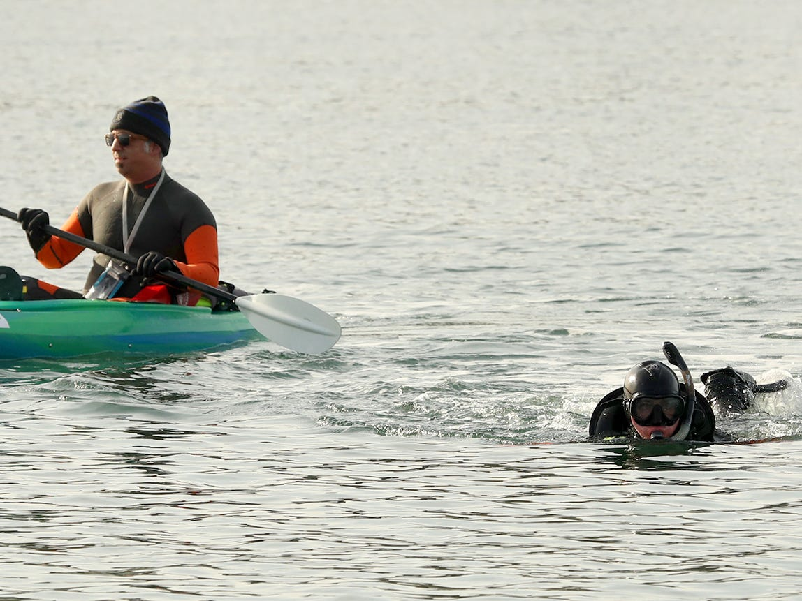 Bremerton firefighter Rickey Muttart (right) swim thourhg the sift current while taking part in rescue swimmer training with Lt. Alex Magallon (in the kayak) off of the shore of the Lions Park Boat Launch in Bremerton on Monday, January 28, 2019.