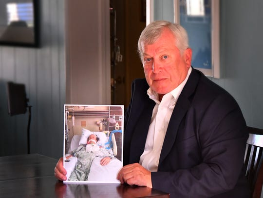 Charles Benoit holds a photo of his late wife, Debbie, at the kitchen table of his Cocoa Beach home.