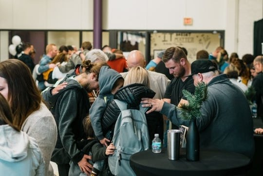 A group praying during a sermon at Centerpoint Church. The church was previously located at Unioto High School before finding a permanent home.