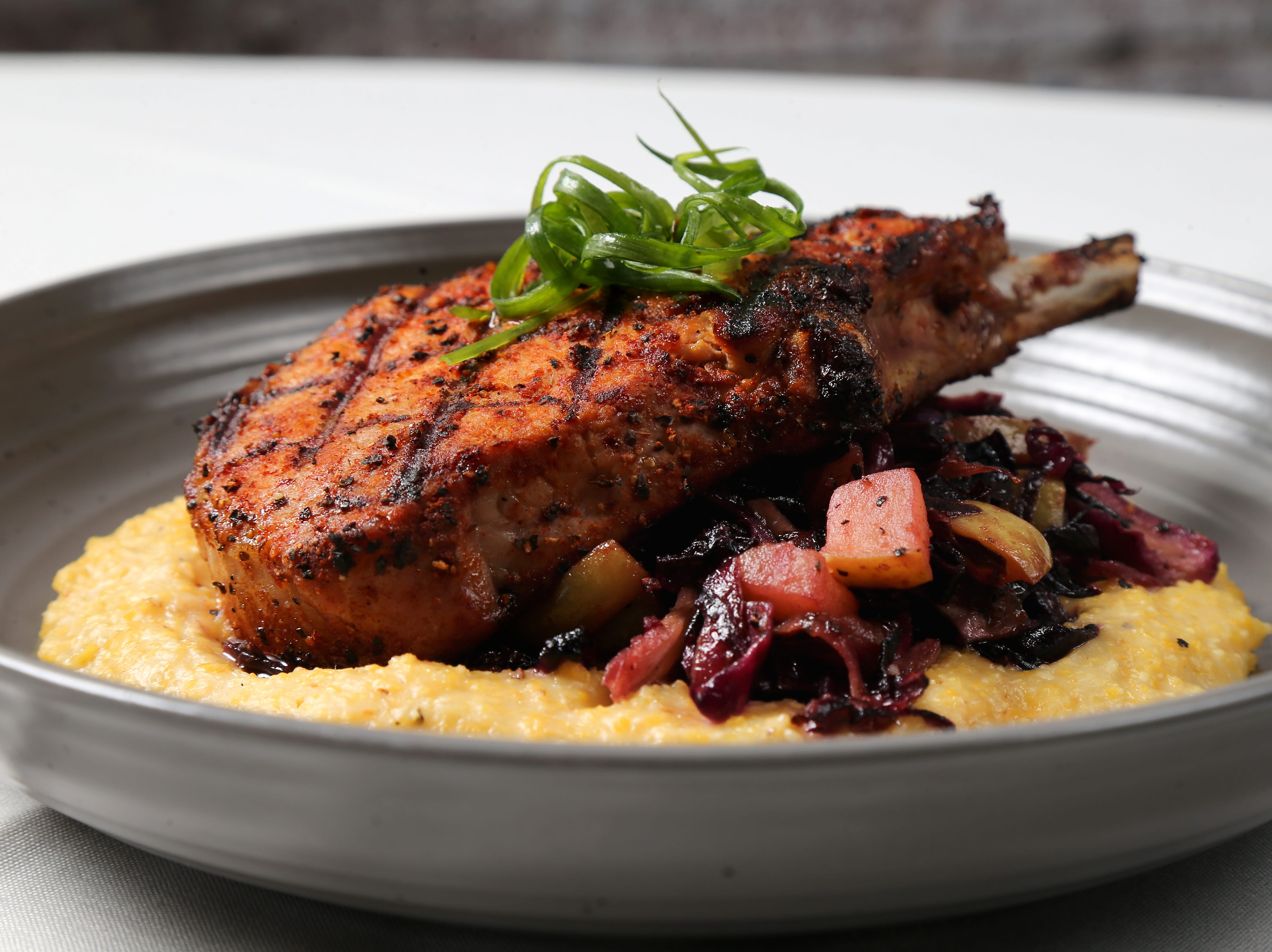 Allegiance Frenched Pork Chop dry-rubbed and smoked, cheddar Geechie Boy grits, hot apple slaw, bacon vinaigrette, pictured, Friday, Jan. 25, 2019, at Tano Bistro restaurant in Loveland, Ohio.