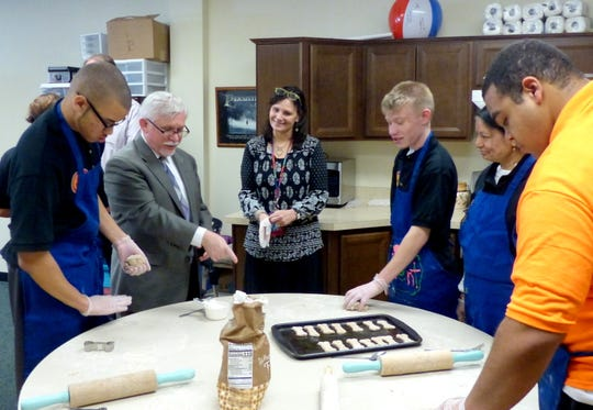 """PAL students and Teacher Marci Rubin share tips about making """"PAL Treats"""" with Middlesex County College Interim President Mark McCormick."""