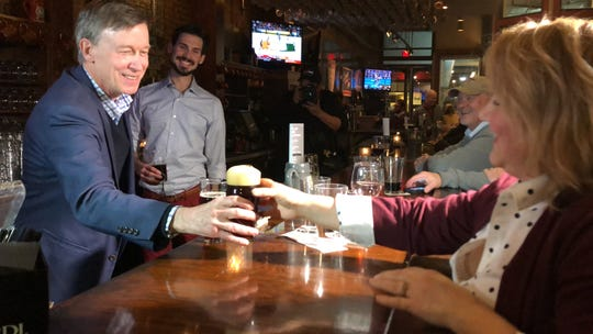 Former Colorado Gov. John Hickenlooper hands a patron a beer during a stop at Court Avenue Brewing Co. Sunday.