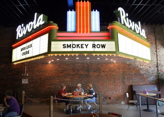 Oskaloosa day in the Life - Underneath an antique neon marquis, Vicki West, left, Cecelia VanRoekel and Elaine Shrader, all of Oskaloosa, eat at Smokey Row Coffee House in Oskaloosa. (Christopher Gannon/The Register)