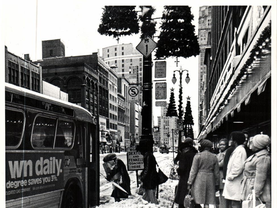 Passengers wait to board a bus on a snow packed sidewalk in front of Hudson's Department Store on Woodward Avenue in Detroit, Michigan after the historic snowstorm of December 1974.