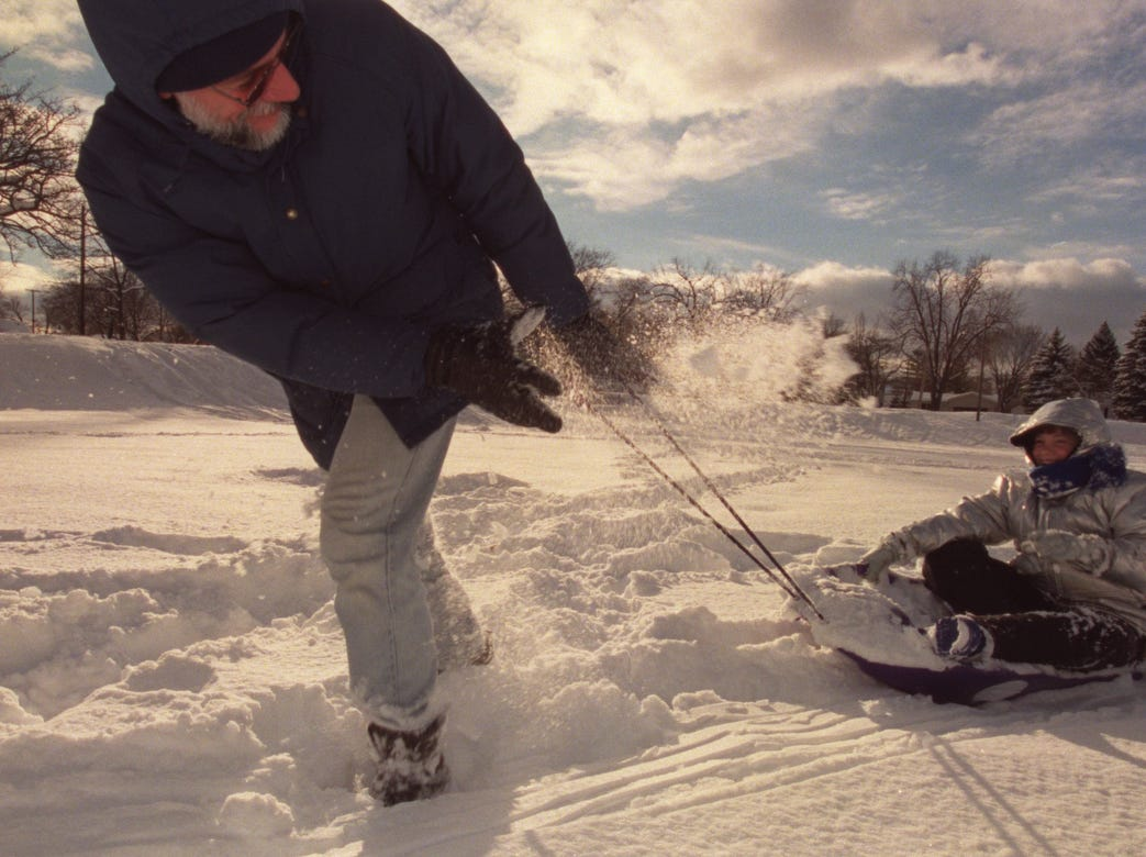 "Automobile engineer John Borza, 48, pulls his daughter Michelle Borza, 12, through the thick snow at Palmer Park in Port Huron, Mich. in 2002. The Borzas drove up from Shelby Township to enjoy the winter weather. ""We heard they had 17 inches up here,"" said Borza. ""It seemed like a perfect day."""
