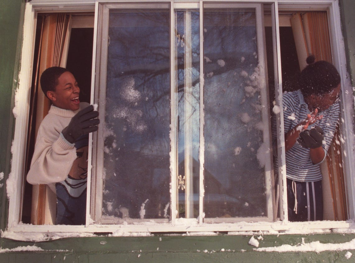 "Seventh grader Alonzo Thomas, Jr., 13, laughs after chucking the first winter snowball at his sister sophomore Whitney Thomas, 16, outside the window of their home in Port Huron, Mich. in 2002.  ""I'm happy about it snowing,"" said Alonzo. ""But I just wish it was on a school day."""