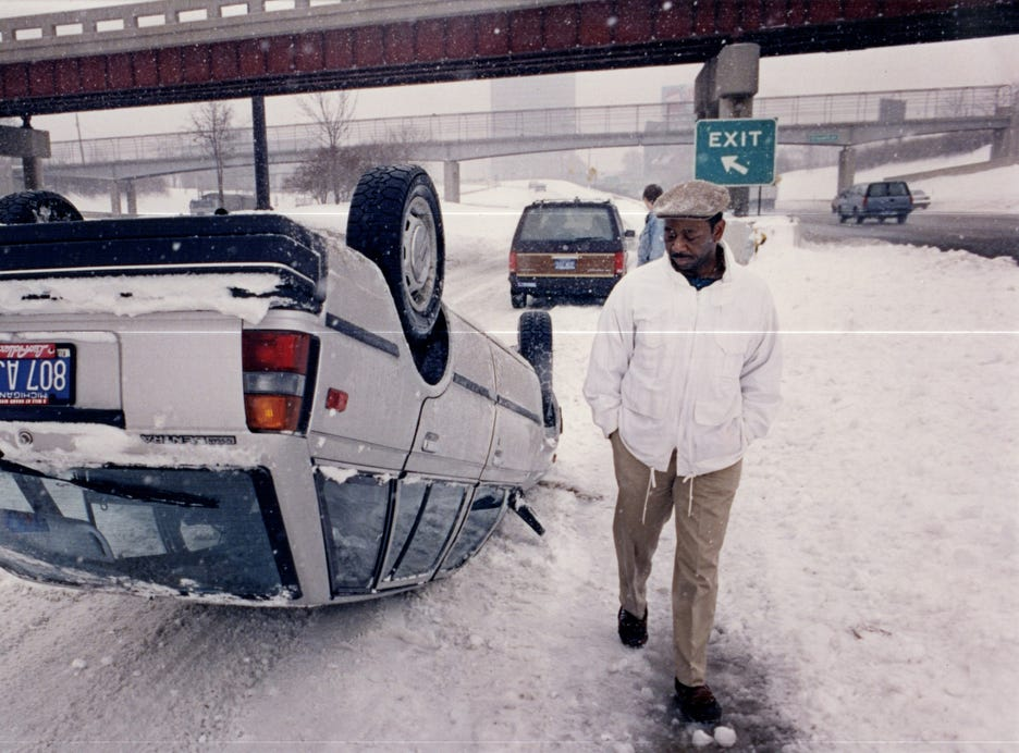 John Riggs, 44, of Detroit, Michigan, strolls around his overturned car on the southbound Lodge Freeway's Bagley exit in this 1992 photo. Riggs' car flipped after he lost control near a bank of snow. His stepdaughter, April Johnson, 8, was with him, but both wore seat belts and neither was injured.