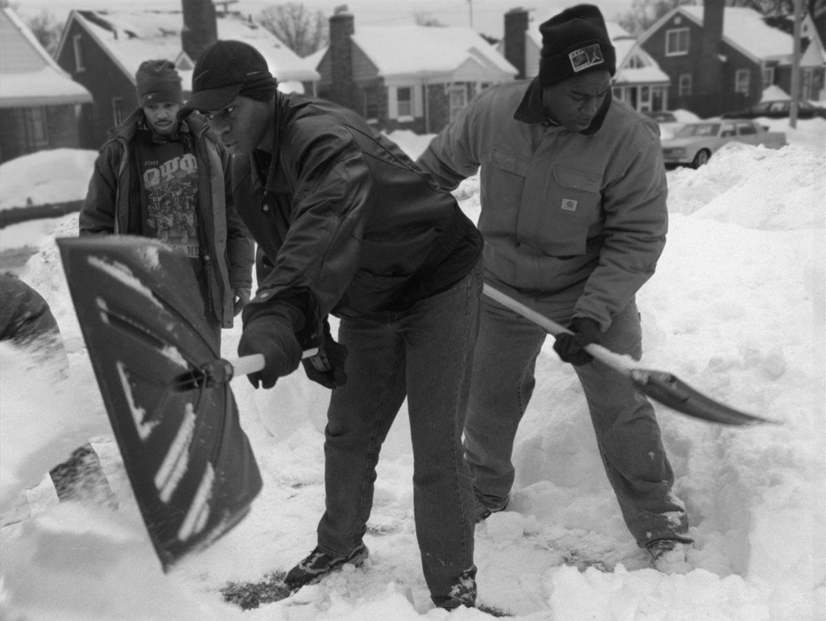 (L-R) University of Detroit students Christopher Wise, 24, Charles Ferguson, 23, and Michael Steward, 26, dig knee high snow from the front yard of Leonida Johnson's home on Saturday, January 16, 1999. Six University of Detroit students volunteered their time and shovels to dig out eight houses in the city of Detroit.