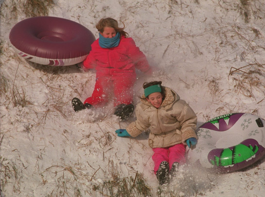 From left, Jessica Ashe, 9, of Beverly Hills, and Kati Everard, 9, of Birmingham, sled down the hill at the Beverly Hills Village Park during a snow day in January, 1999.