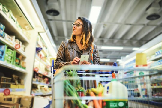 Shot of a young woman using a mobile phone in a grocery store.