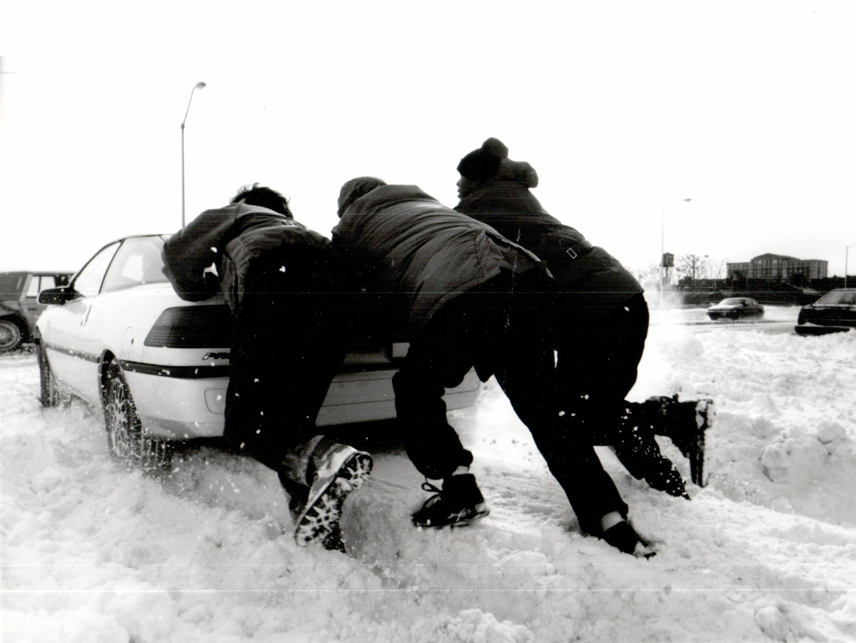 Thomas Byrnes, Detroit along with Malik Salaam and another man who preferred to remain anonymous, push Dan Mancuso's car out of the snow near Jefferson avenue in Detroit in 1992.