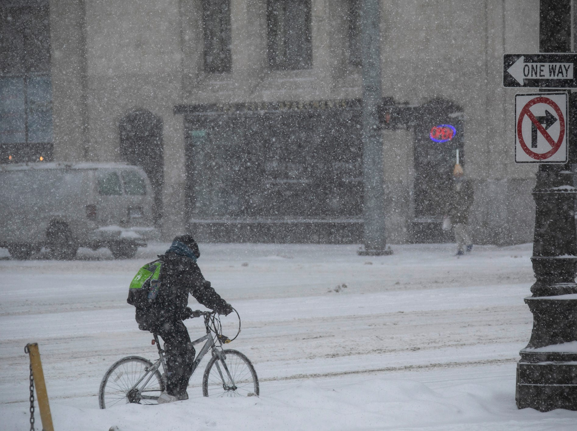A brave cyclists rides their bike northbound on Woodward Avenue as heavy snows cover the area on Monday, Jan. 28, 2019.