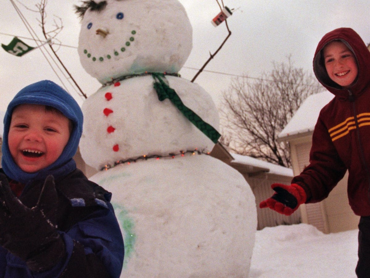 Michael Kirschner (left), 4, and Tyler Witte (right), 10, of Troy, play tag in the driveway of their neighbor Kim and Tom Johnson's home on Kilmer street in 2000. A handful of mischievous neighbors constructed a 16-foot-tall snowman.