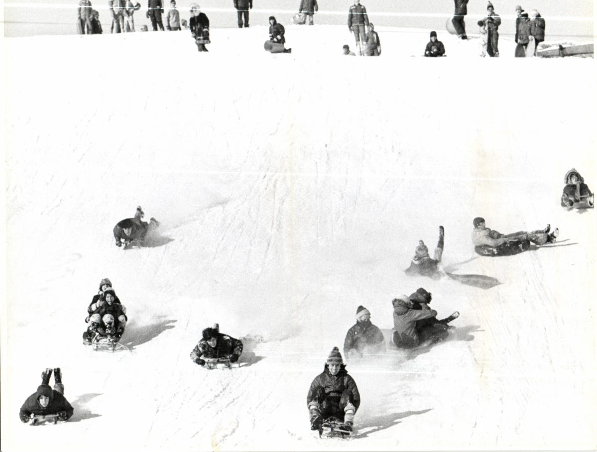 The snow is a welcome sight on Dead Man's on Hines Drive in Detroit, (right), where sleds and discs carry downhill enthusiasts at a sometimes dizzying pace in 1979.
