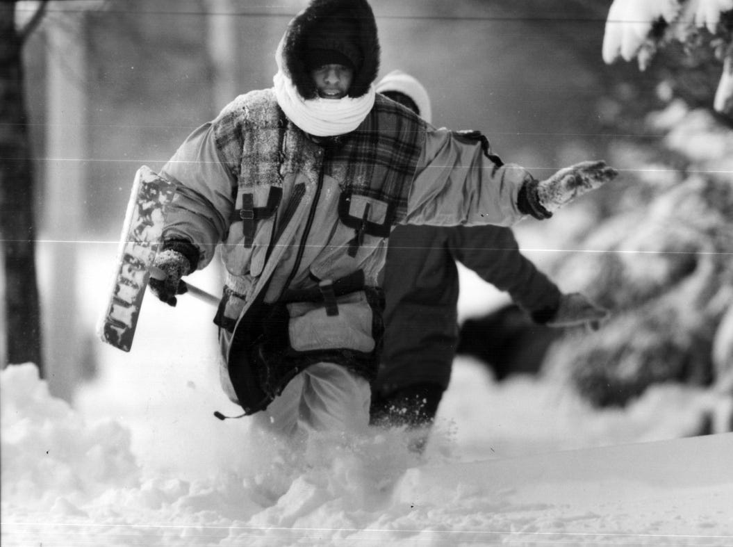 Christal Sims, home from school, runs down Larned near McDougall, after helping a neighbor shovel snow in Detroit in 1993..