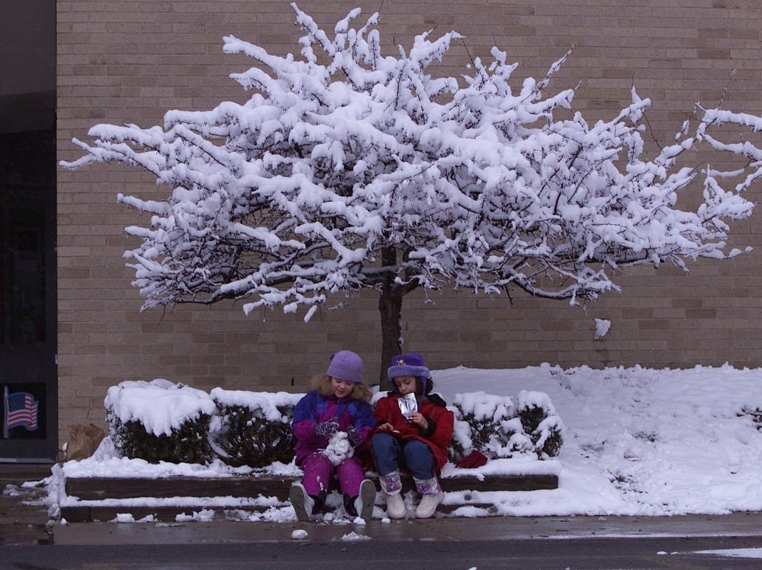 First graders Kayla Porter and Senada Cosovic, both 7, have their snack break outdoors at Bemis Elementary school in Troy in 2002.