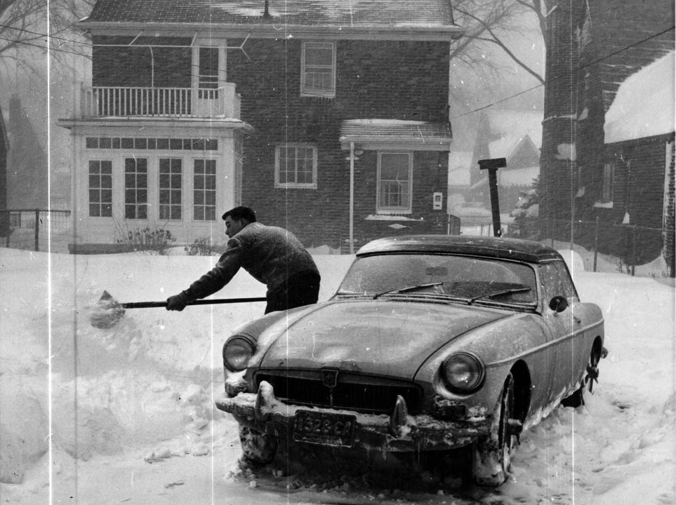 A man shoves his car out of the snow after a 1965 storm in Detroit, Michigan.