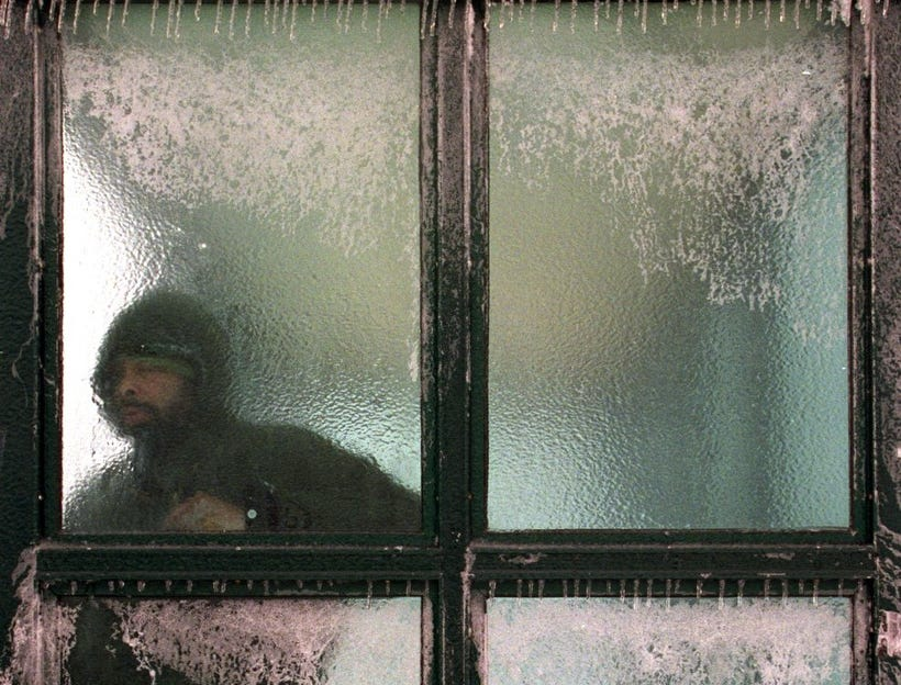 Johnathon Butler, from Detroit, waits in a ice covered bus stop shelter at the corner of Mack and Conner Thursday January 31, 2002 as snow gave way to freezing rain during a winter storm that blasted the metro area.