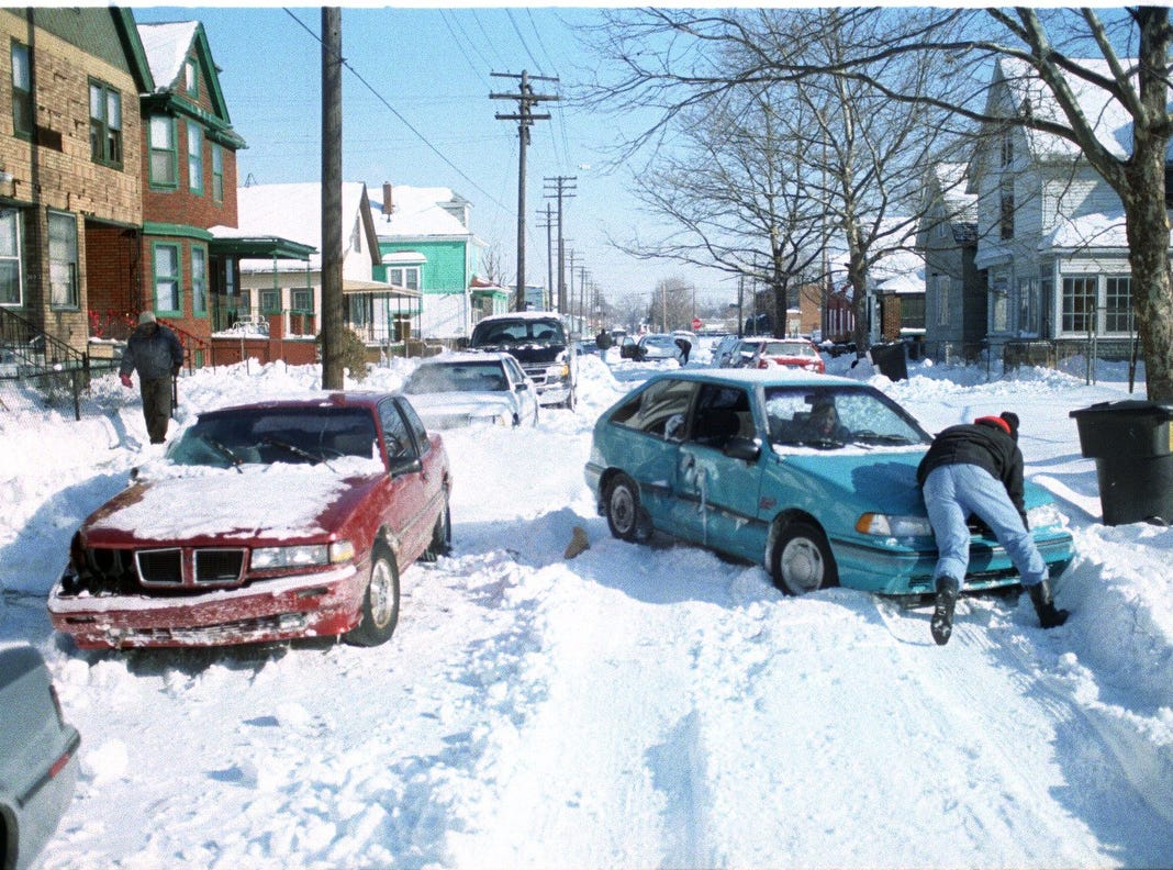 Residents look to free their cars from a snowy street in this scene in January, 1998.