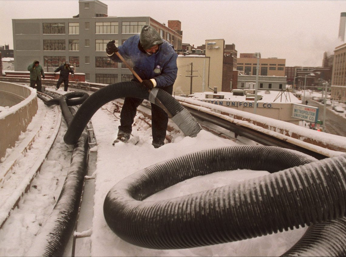 Derrick Rhodes, of Power Vac Services in Detroit vacuums snow from the people mover tracks on January 12, 1999, near the Greektown station.