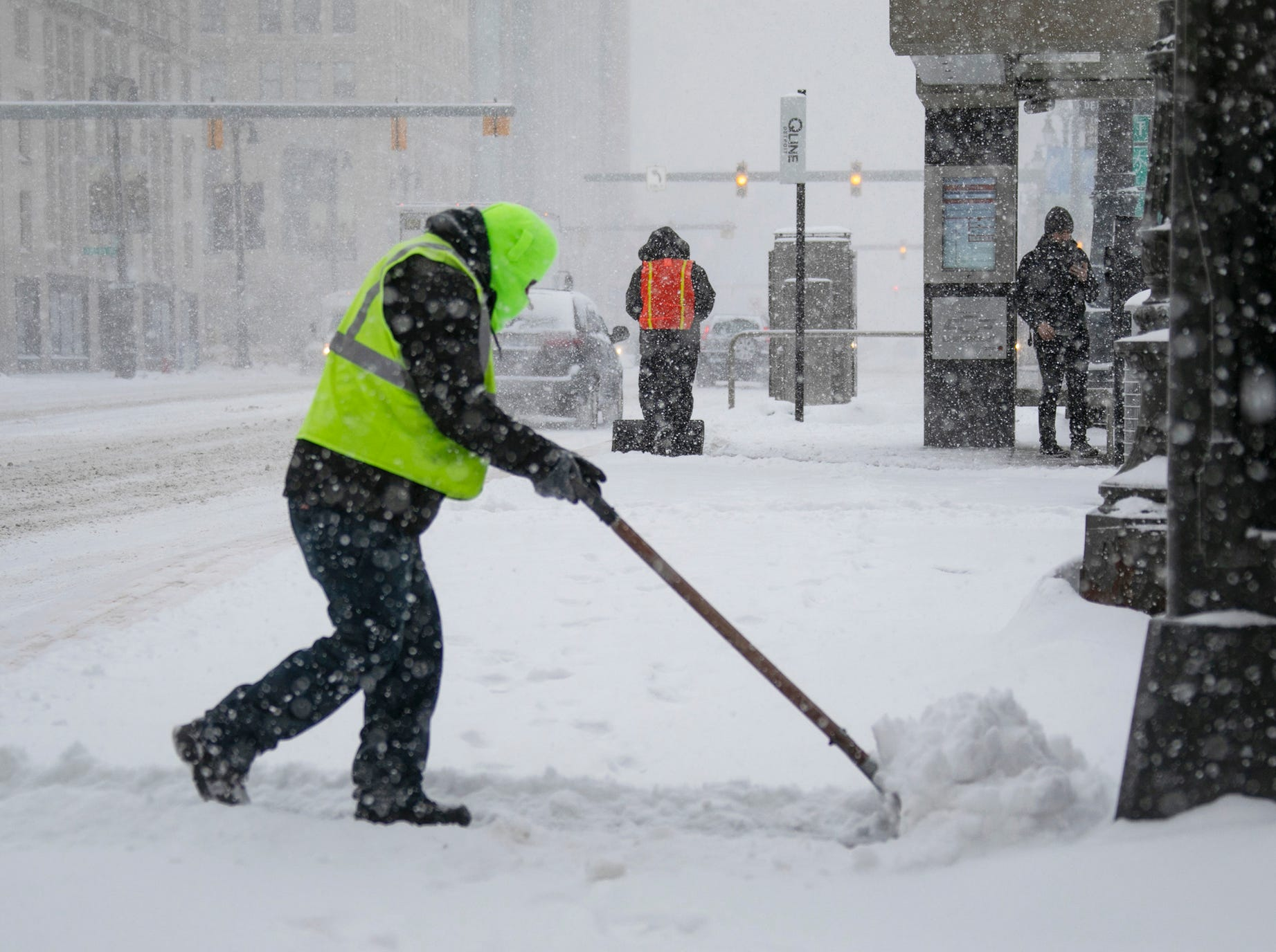 Qline employee Jorge Aguilar shovels snow at the Grand Circus Qline stop as heavy snows hit metro Detroit on Monday, Jan. 28, 2019.