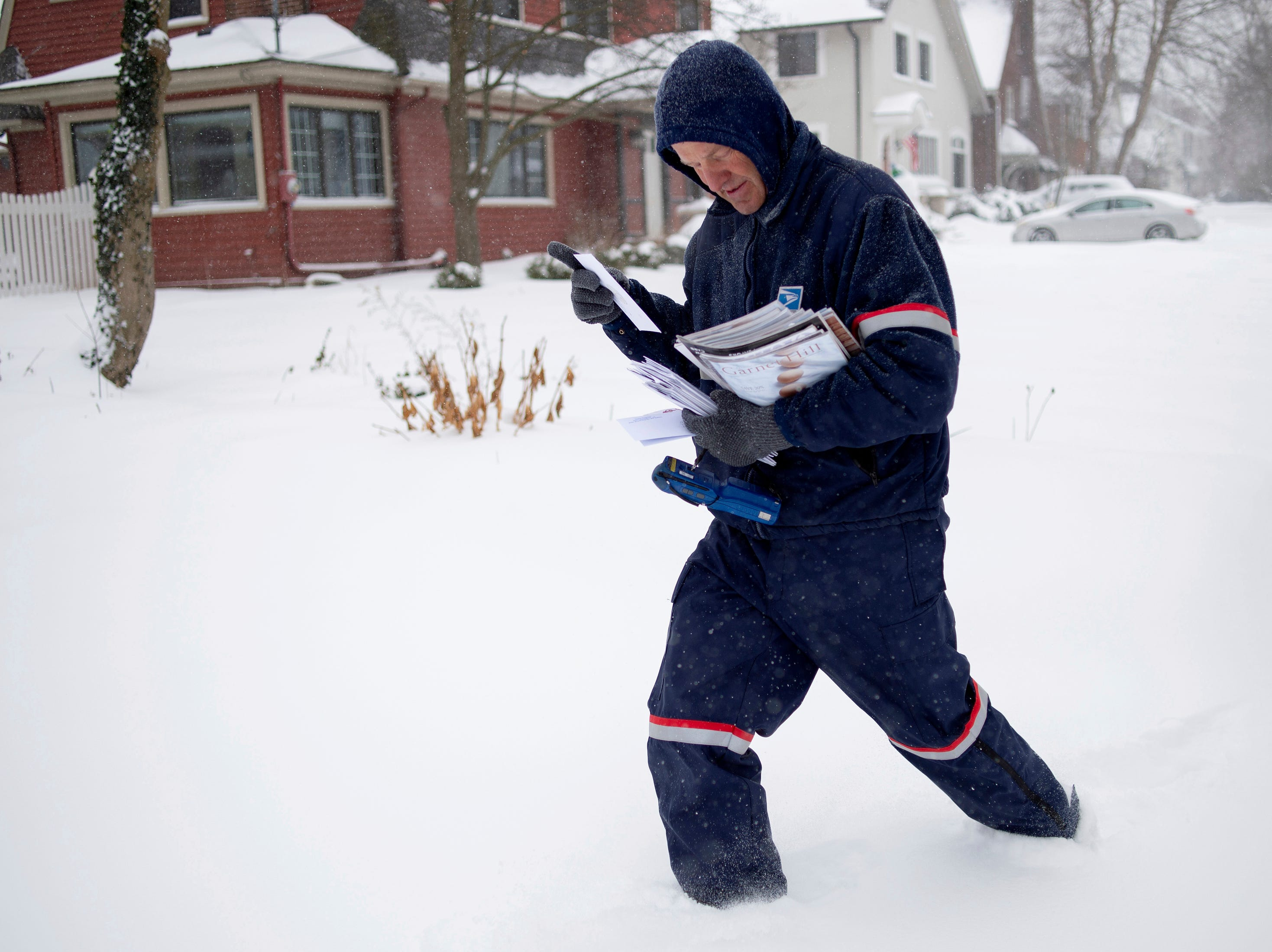 United States Postal Service letter carrier Keith Caniff sorts mail on his route in East Grand Rapids, Monday.