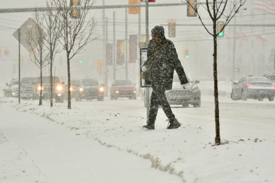 Pedestrians and vehicles make their way through snowy streets on Evergreen in Southfield, January 28, 2019. ()