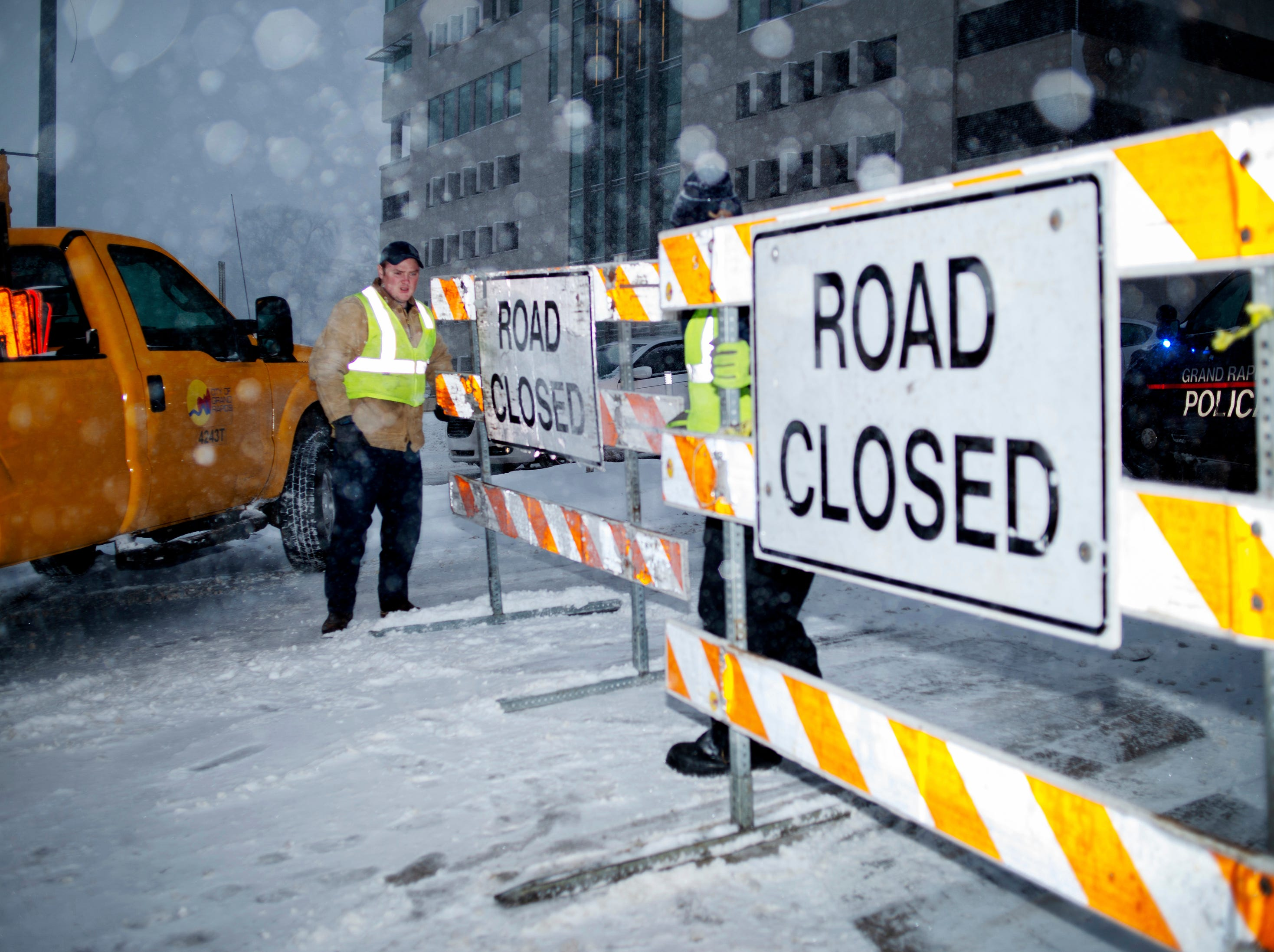 City workers put up a road closed sign on the Michigan Street hill in Grand Rapids, Monday morning.