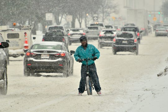 Despite the snow, Ron Johnston, of Ferndale, rides his bicycle home on Eight Mile Road in Oak Park, January 28, 2019.
