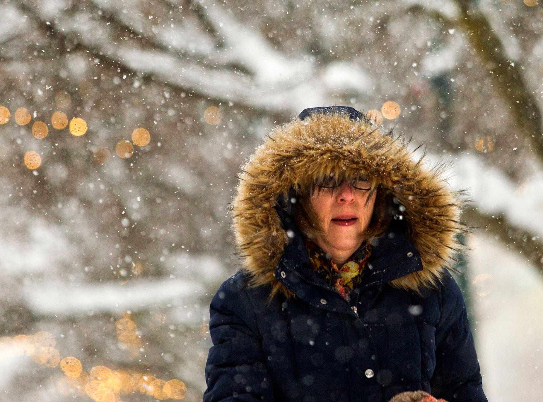 Theresa Breen walks through the snow to work in downtown Traverse City Monday.