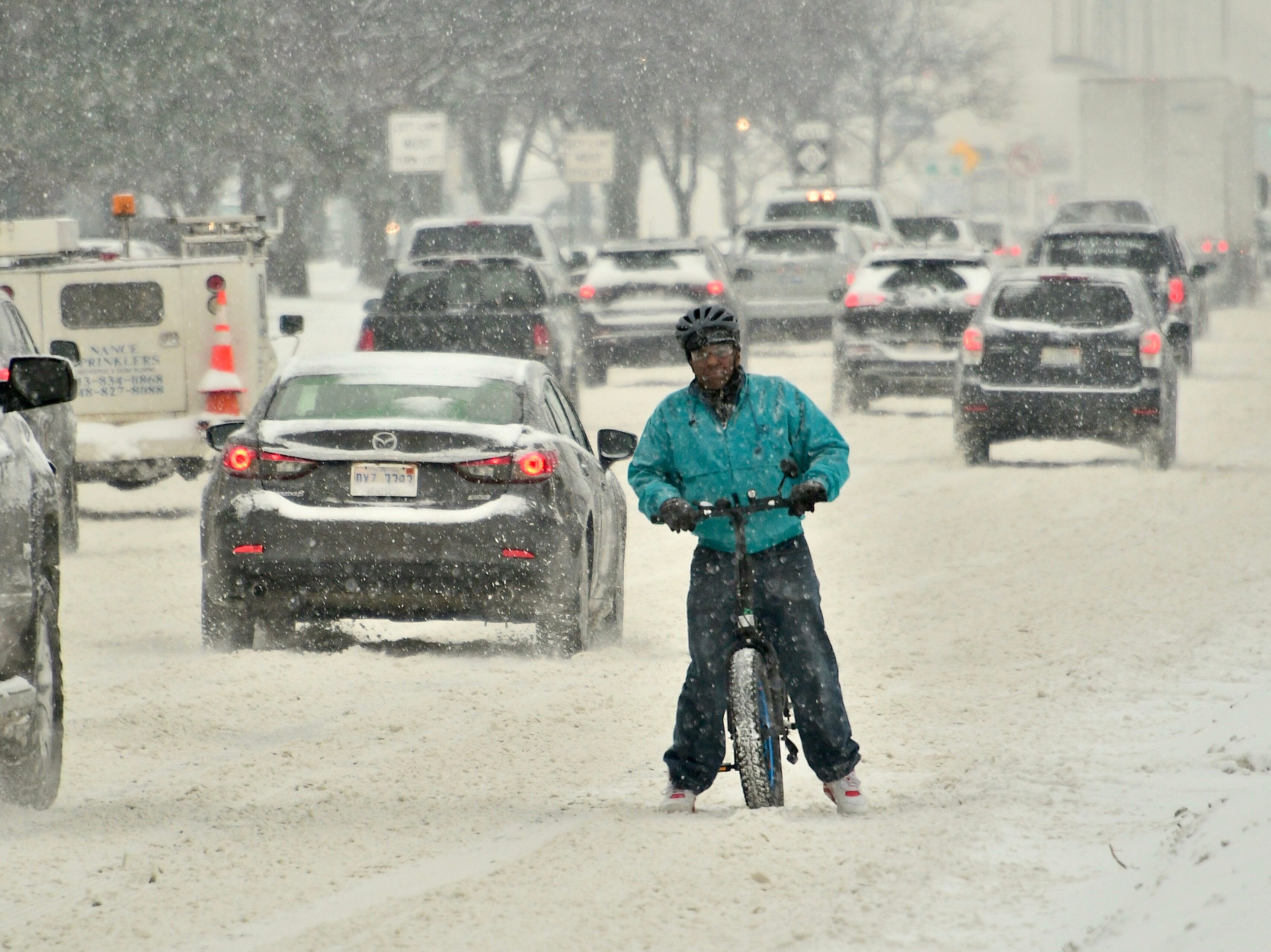 Despite the snow, Ron Johnston, of Ferndale, rides his bicycle home on Eight Mile Road in Oak Park, Monday afternoon,  January 28, 2019.  Snow and gusting winds created blizzard-like conditions Monday across  the state, prompting closures of many schools, government offices and businesses, and   snarling air travel.