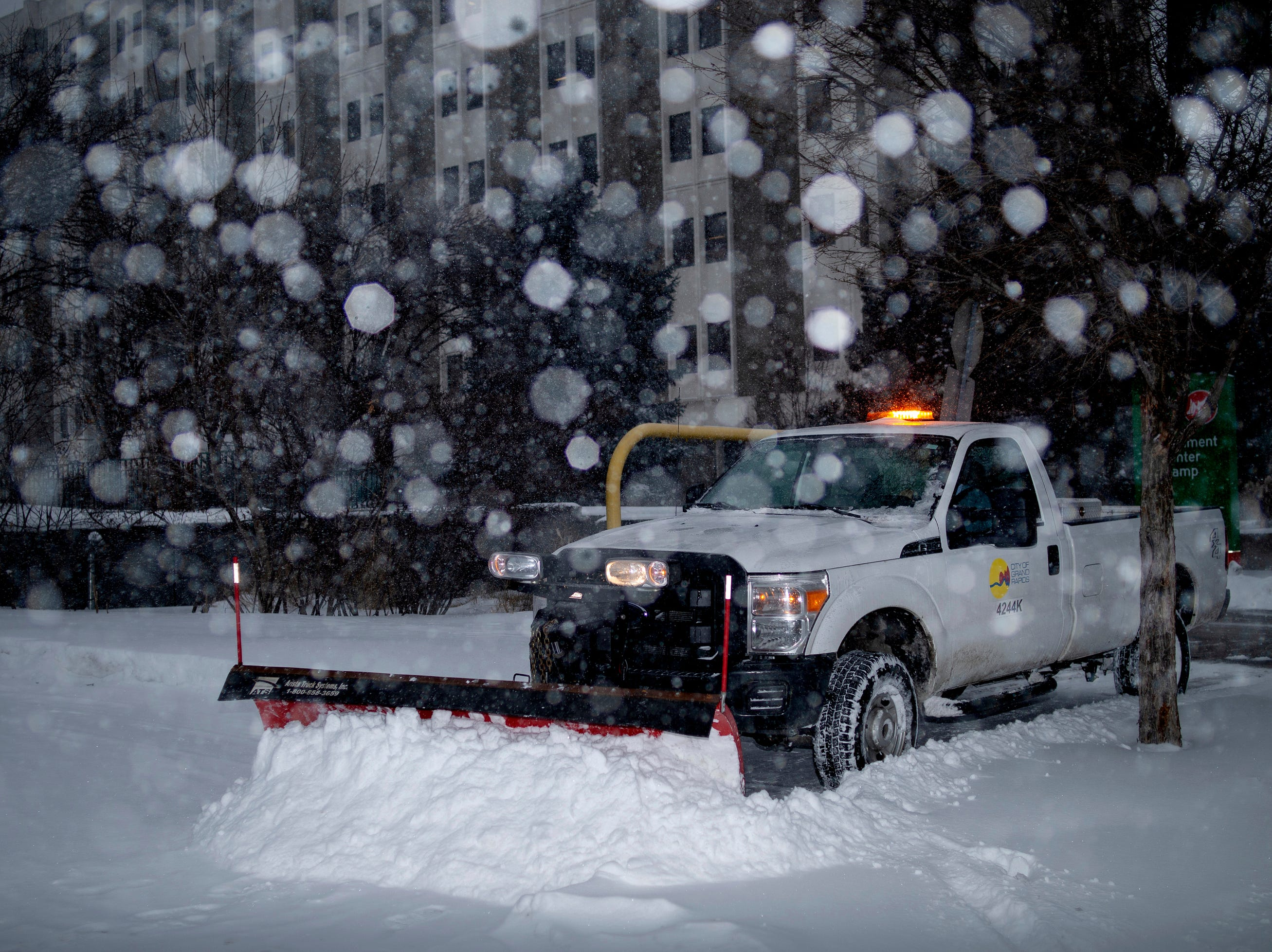 A city worker plows a sidewalk in Grand Rapids Monday morning.