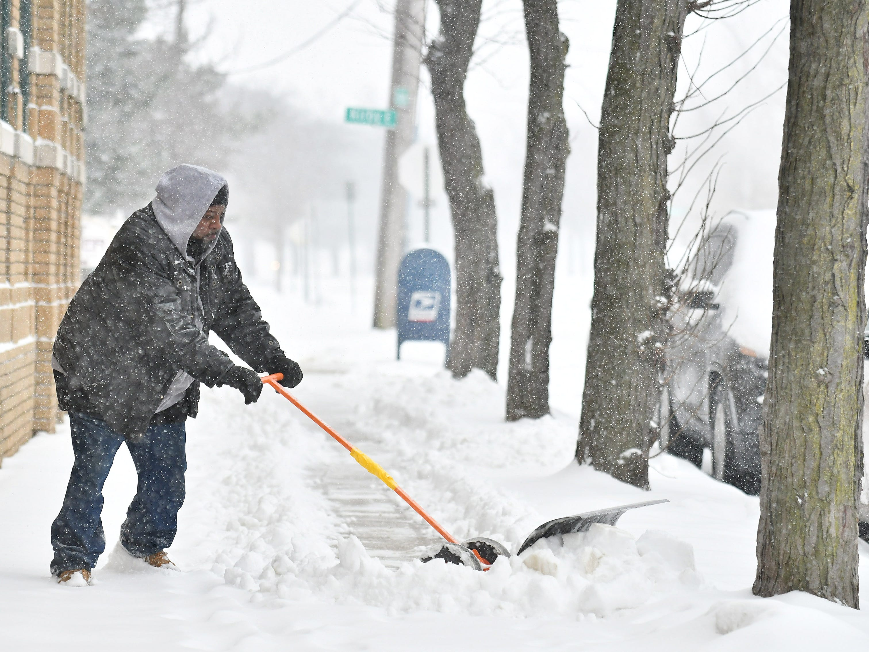 """Walter Houze uses a rolling shovel to remove snow from the sidewalk outside the Kirby Lofts in Detroit on Jan. 28, 2019.  Houze says, """"It works as good as a snowblower and I don't have to buy gas for it."""""""